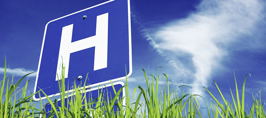 image of the hospital logo amid grass and a blue sky