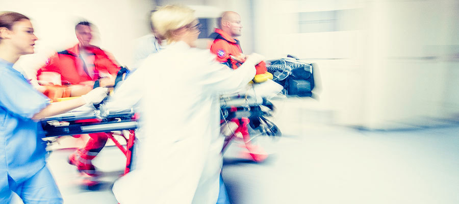 clinicians running with a patient on a gurney