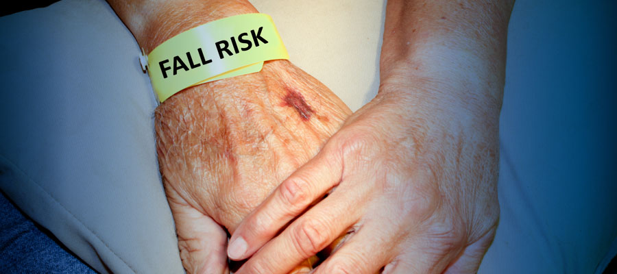 "Image of senior's hand with paper bracelet that says ""Fall Risk"""