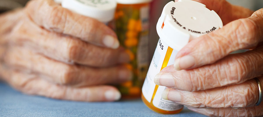 Elderly person's hands holding prescription bottles