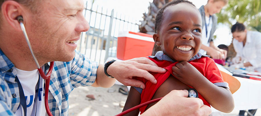 man with stethoscope examining young boy, who is smiling