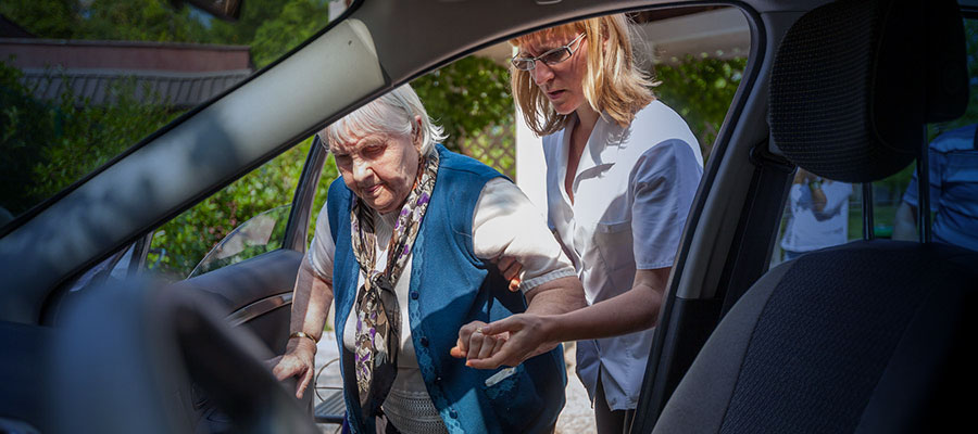 elderly woman helped into car by younger woman