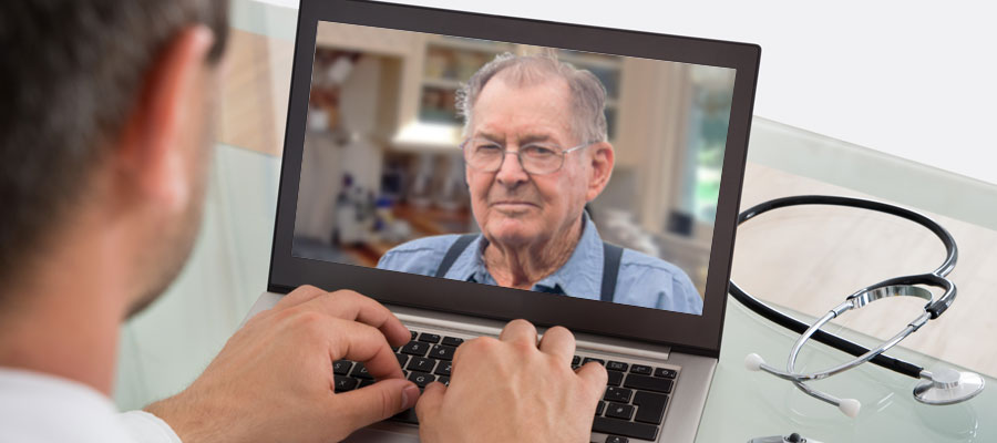 image of physician typing into a laptop with an image of man in suspenders on the screen