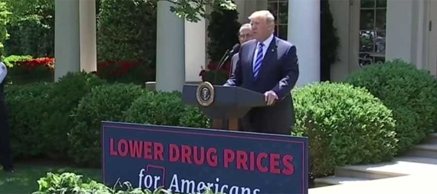 "Image of Trump speaking outside of White House with banner that says ""Lower Drug Prices for America"""