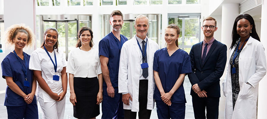 Group of clinicians standing in lab coats and scrubs