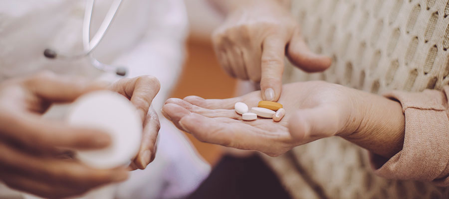 Picture of a hand touching prescription pills