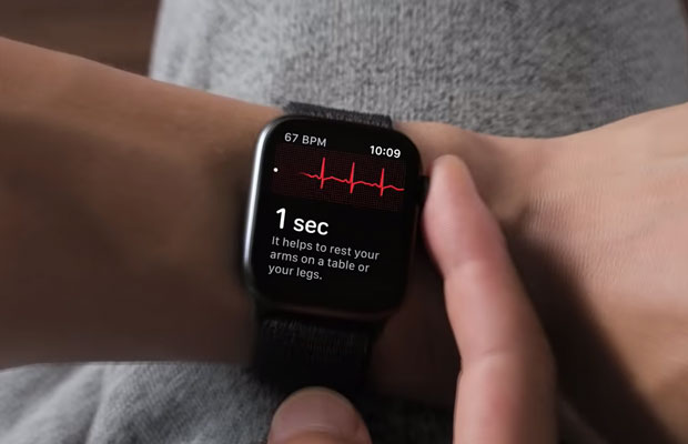 Could Emerging Sensors Revolutionize Wearable Technology? Person tapping on smartwatch with heart monitor visible on it.