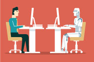human sitting at computer across from robot sitting at computer