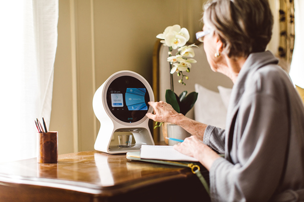 Innovative Devices Engage Patients in Their Health — at Home and on the Run. A woman accesses a standalone desktop device with a touch screen to access medical care.