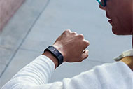 AHA Market Scan Fitbit Forms Its First Partnership with Medicaid Plan. A man looking at his Fitbit on his left wrist.