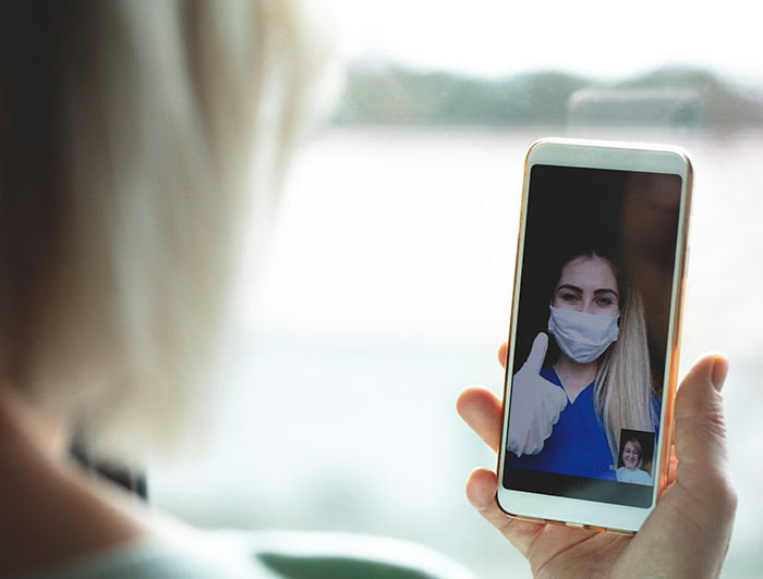 Patient using technology to interact with nurse during COVID-19 pandemic