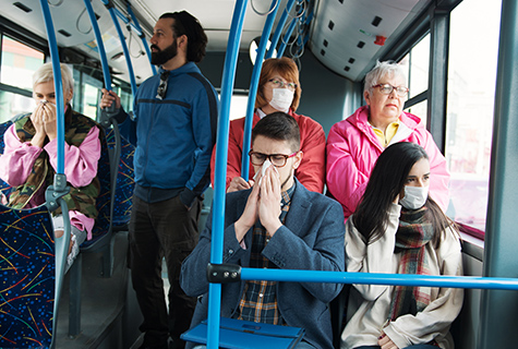 stock photo of crowded bus with some sick riders and other riders wearing masks