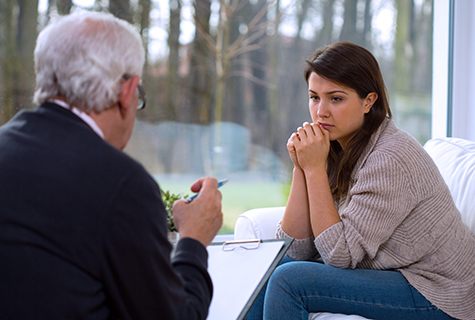 woman seated on sofa speaks to counselor