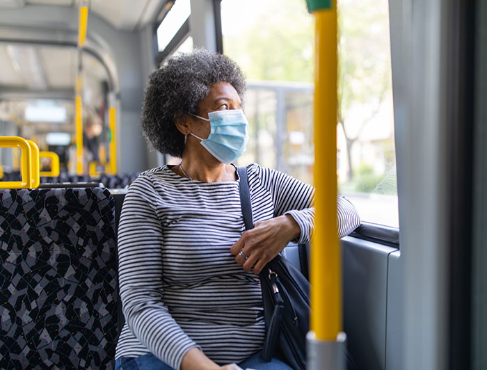 Lady sitting on bus looking out window with mask on