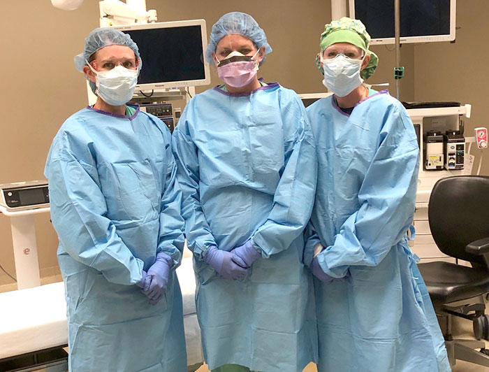 three nurses standing together with full gear on