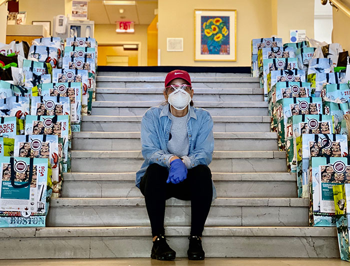 Staff member sitting on stairs between bags of to distribute during the COVID-19 pandemic