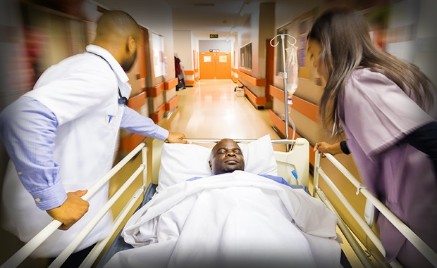 Stakeholders Target Health Disparities During Pandemic. Emergency room clinicians transfer an African-American patient down a hospital corridor.