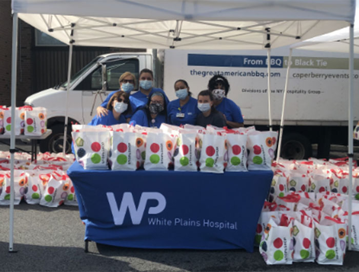 White Plains Hospital volunteers stand with bags of food to be distributed