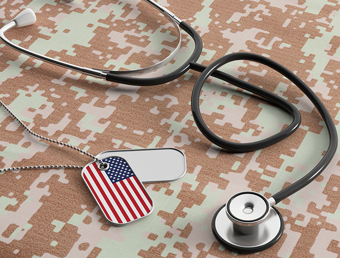 Dog Tags, one with an American Flag laying with a stethoscope on camouflage