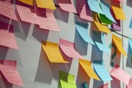 Intermountain Healthcare CEO Shares Takeaways from COVID-19. Many different colored Post-It notes with writing on them stuck on a white board.