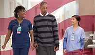 two health workers walk with patient down hospital hallway