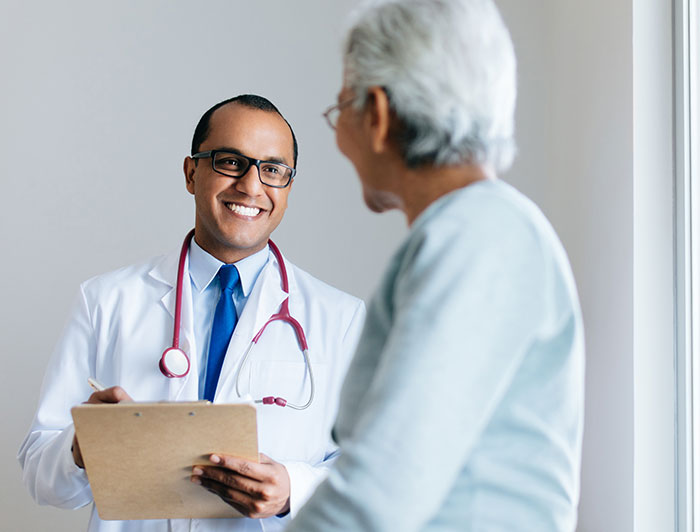 Age-friendly doctor smiling at older female patient