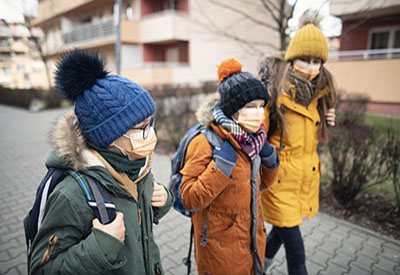 people in winter clothes wearing masks