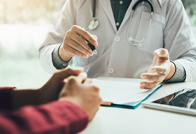 doctor sitting at desk talks to patient