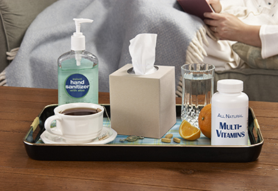 sick person sits on sofa with tray of illness preventions and remedies in front of them - tissues, vitamins, tea, hand sanitizer
