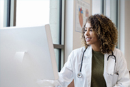 AI in Health Care: Leading through Change. A female doctor works with AI while looking at a computer monitor.