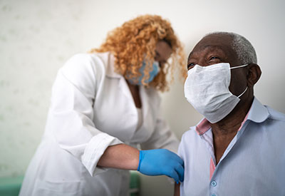 female health worker wearing mask preps older male patient, also masked, for injection