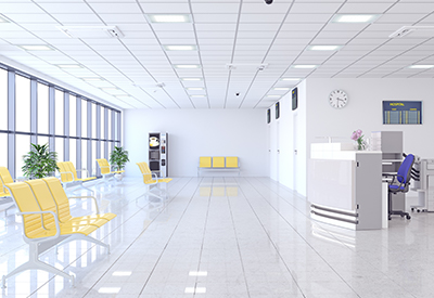 Empty, bright white hospital waiting room/lobby with yellow seating arranged on the left side of the image and reception desk on the right