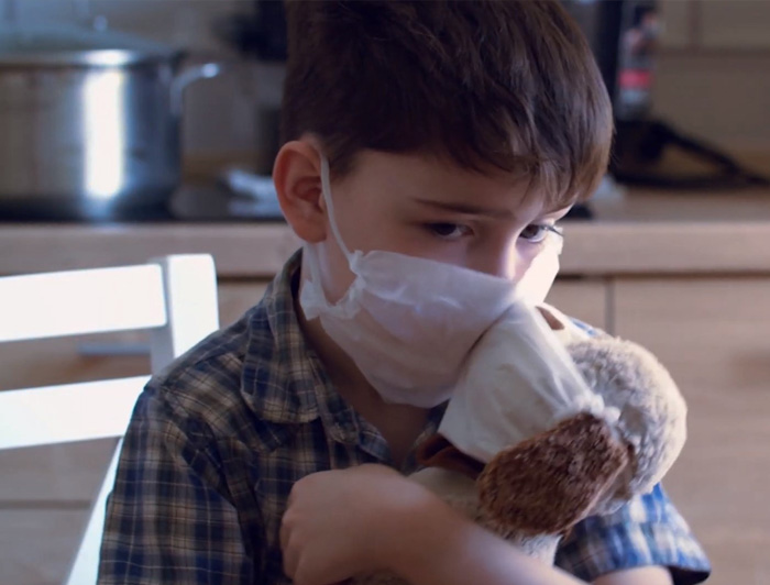 Boy with mask holding a plush puppy with a mask on