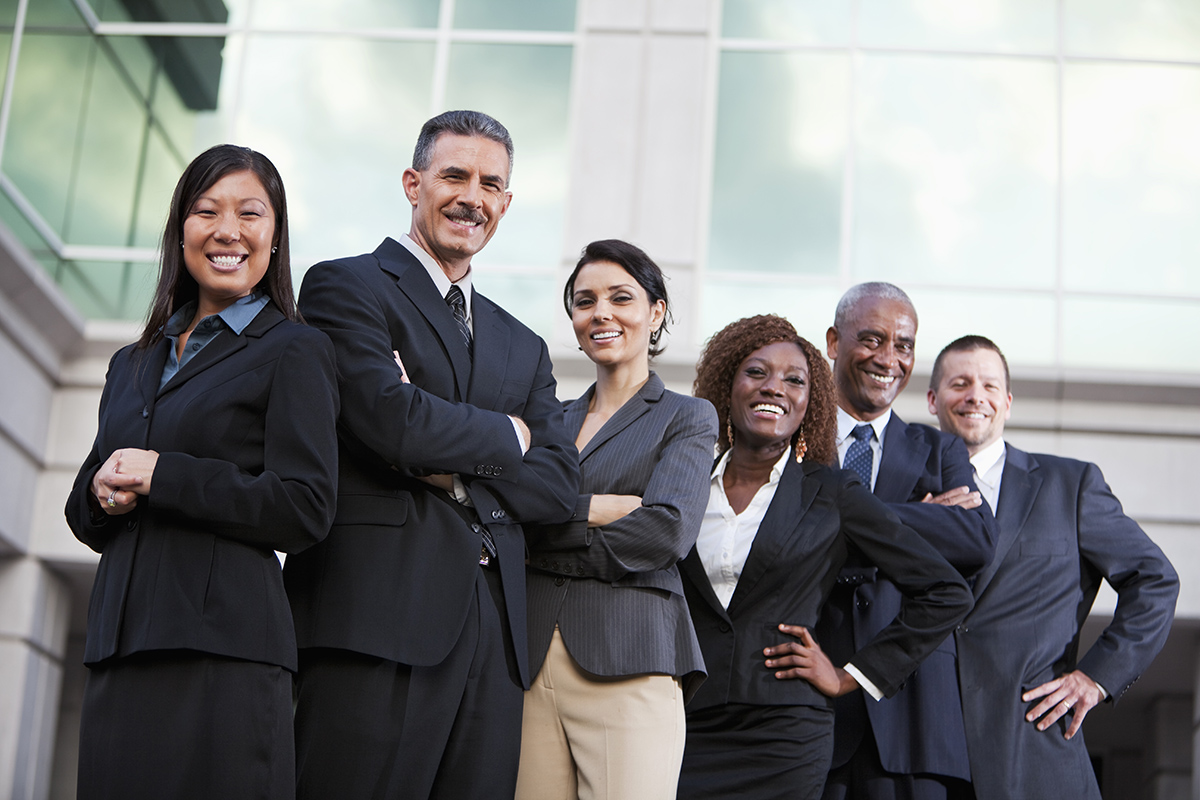 diverse group of business people standing in front of a building smiling