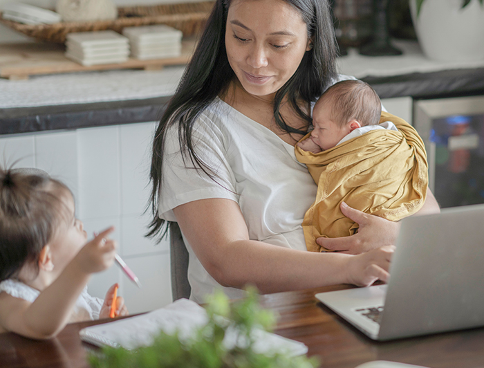 stock photo of mother seated at a table with a laptop and notepad. Woman is holding an infant and engaging with a toddler