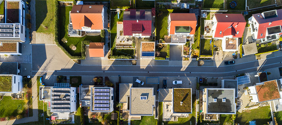 To Advance Health Equity, You Must Invest in Communities. An overhead photo of a street in a neighborhood with large, two-story houses on both sides of the street.
