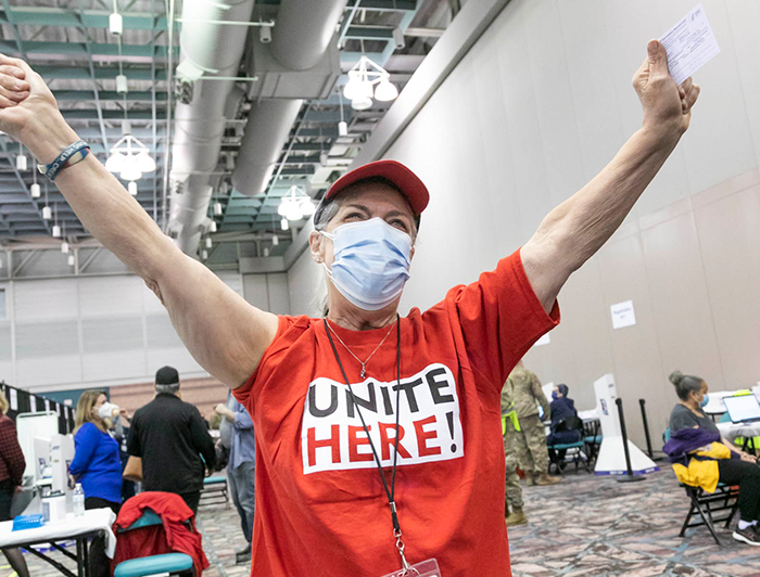 Person at AtlantiCare vaccination event stands with arms raised in celebration