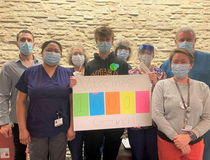 Health workers wearing masks stand around posterboard that reads '10000 vaccines given!!''