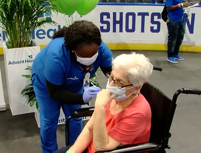 Female AdventHealth worker stands over female patient in wheelchair and administers vaccine
