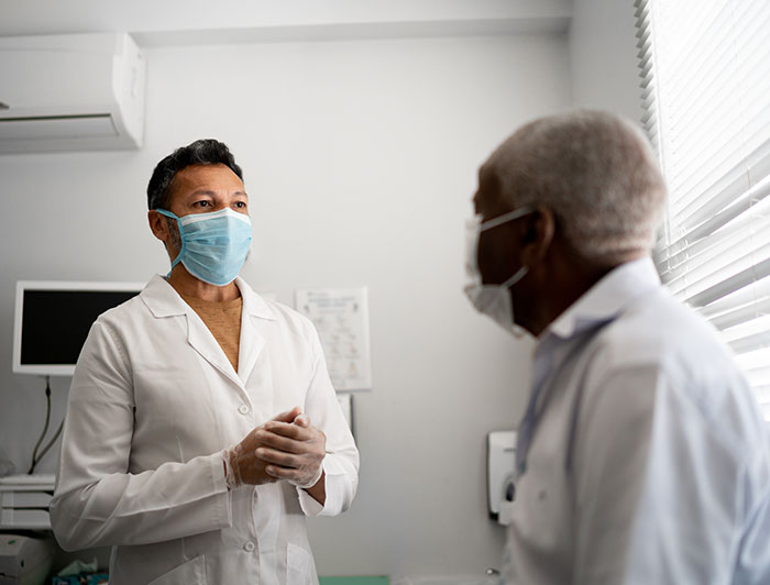 physician and patient wearing medical masks speak in examination room