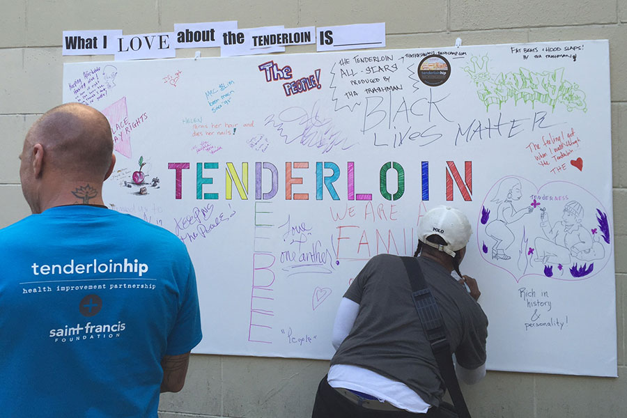 people signing a poster about the tenderloin