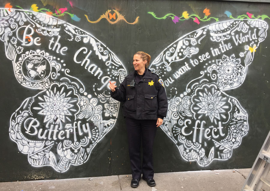 police officer in front of chalk drawing of butterfly