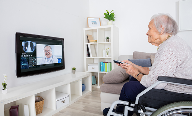 Whoever Controls the Remote May Win with Telehealth. Elderly woman at home in wheelchair speaking with doctor through her television.