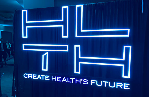 AHA Market Scan More Big Market Transformation Moves in Store Next Year. HLTH Create Health's Future neon sign.