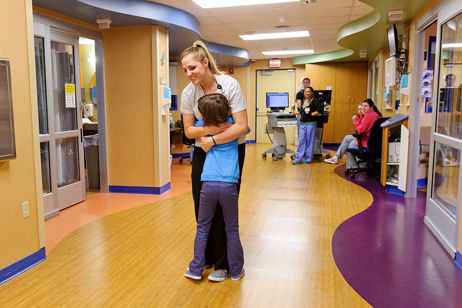A pediatric patient hugging a nurse