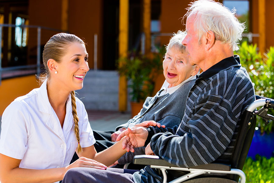 CAPC A nurse speaks with an elderly couple outdoors at a rehab facility.