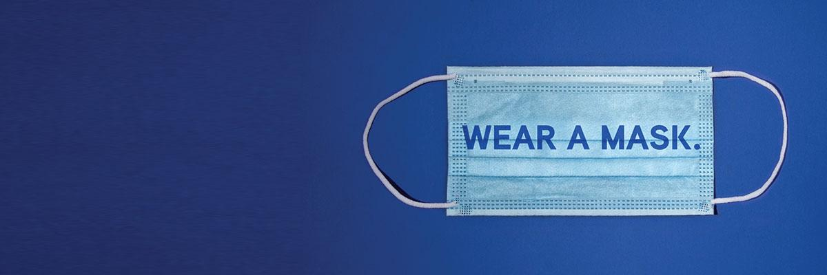 "Phrase ""Wear A Mask."" imposed over a surgical face mask on a blue background."