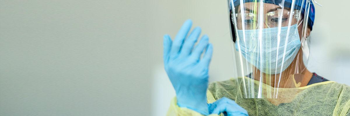 Project Firstline homepage carousel banner. A female clinician wear a gown, surgical mask, and face shield dons a pair of nitrile gloves.