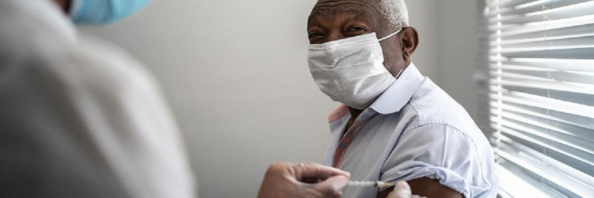 COVID-19 Vaccine. A elderly man of color wearing a mask receives a COVID-19 vaccine in his right arm from a masked, gowned, and gloved clinician.