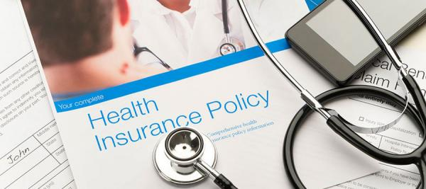 "paper that says ""health insurance policy"" under stethoscope"